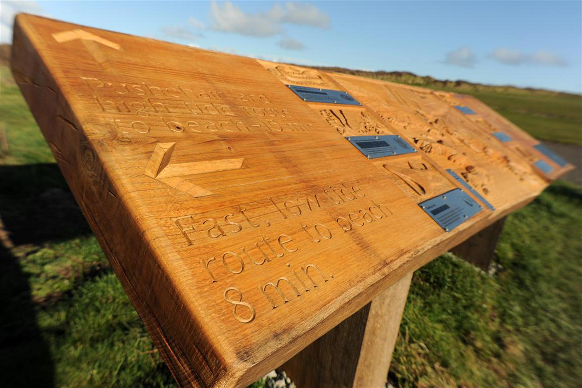 Hand carved way finding arrows within sign for National Trust at Kynance Cove