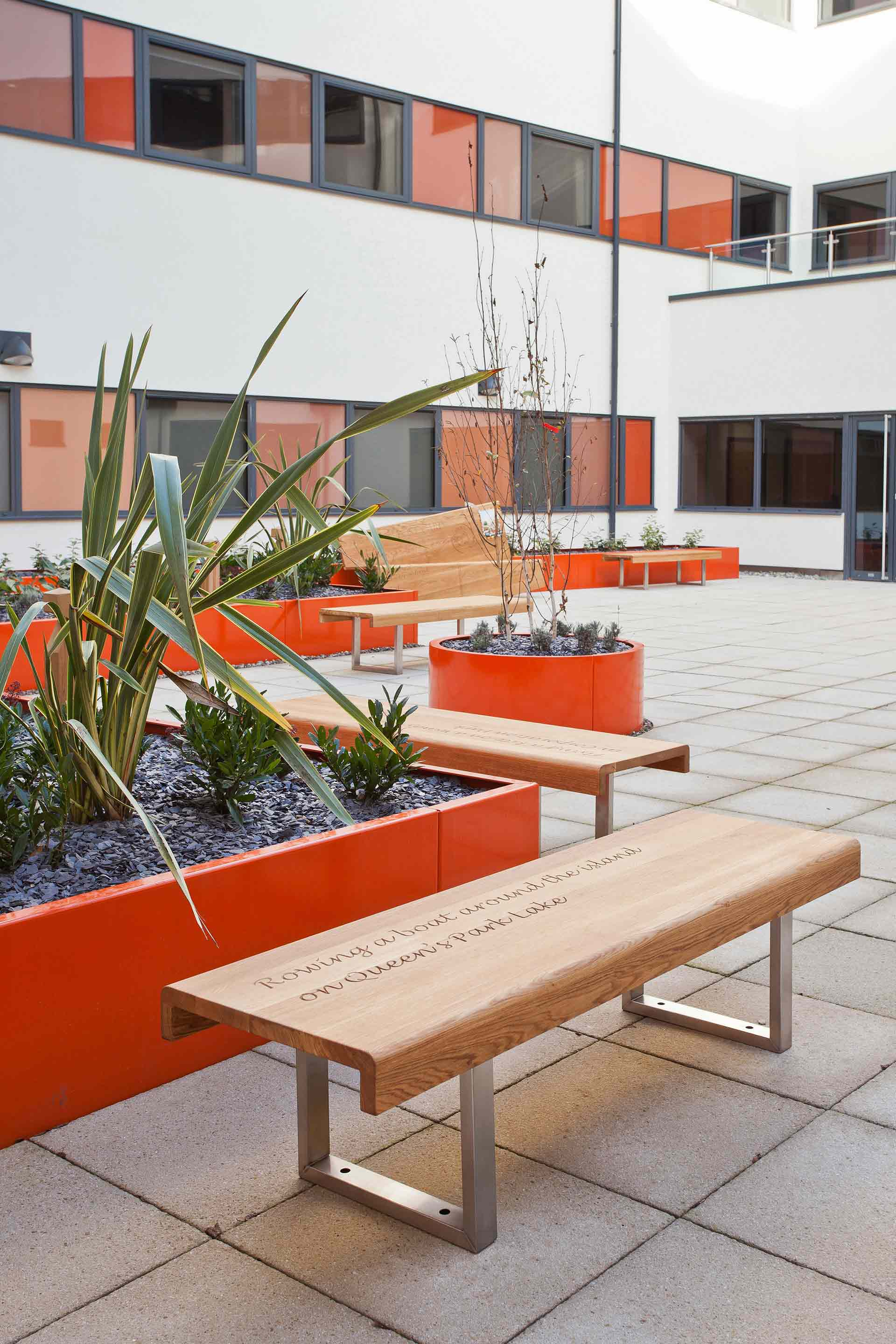 Timber top bench with hand engraving in NHS courtyard