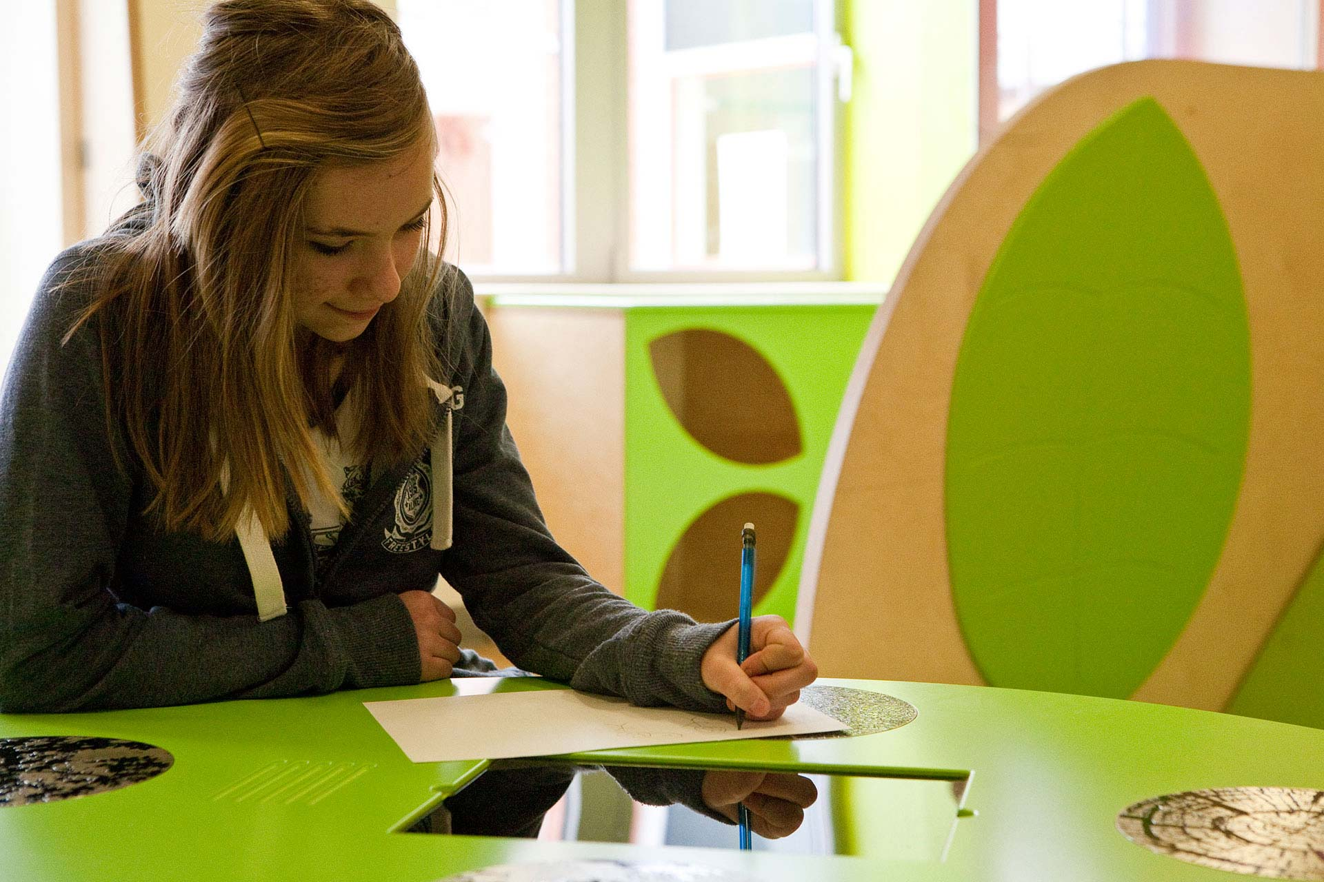 Teenagers using interactive table in waiting room at Salisbury District Hospital
