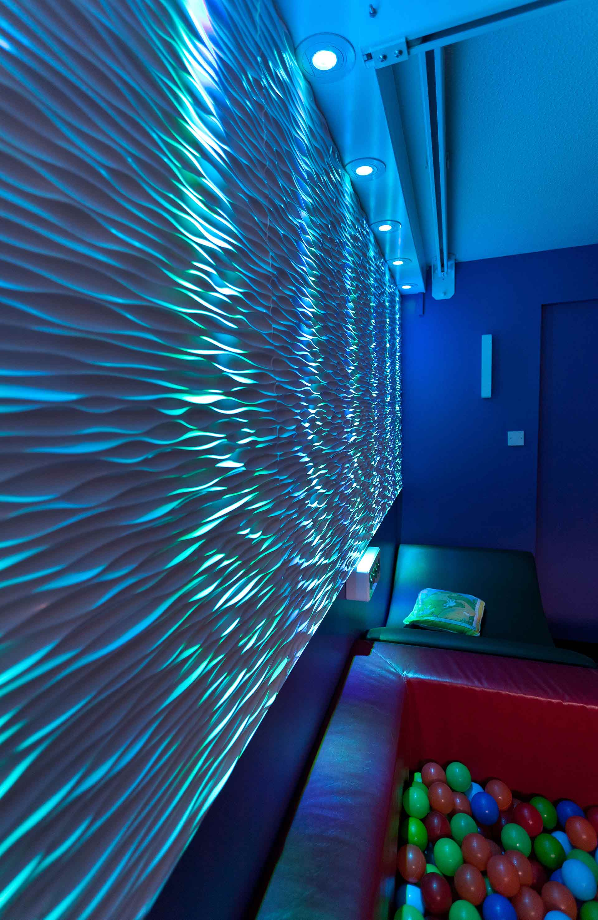LED ambient lighting highlights tactile wall in sensory room designed by Boex