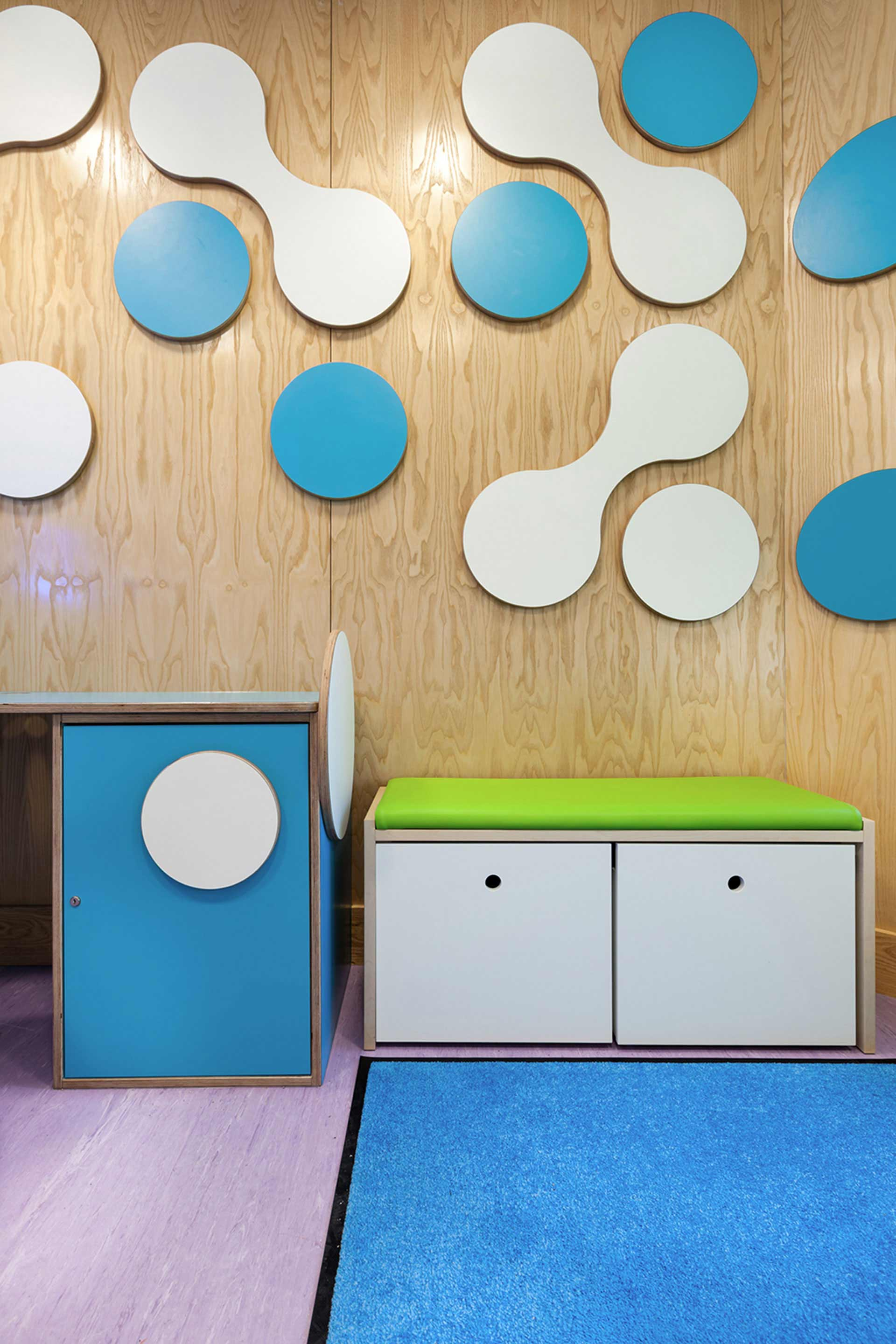 Practical storage with upholstered seat pad in day room for Addenbrookes Paediatric Day Unit