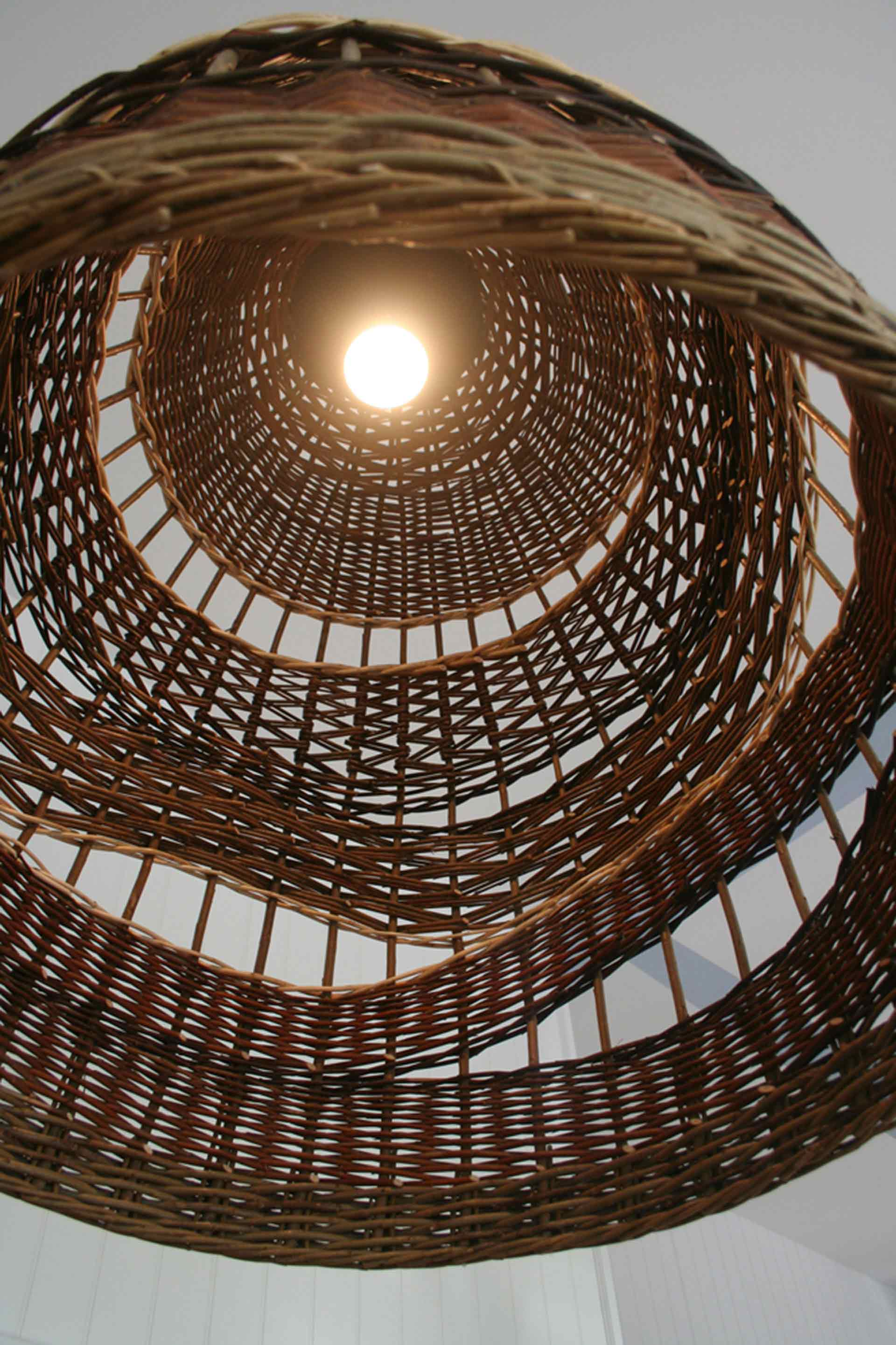 Light fixture within wicker wave shade