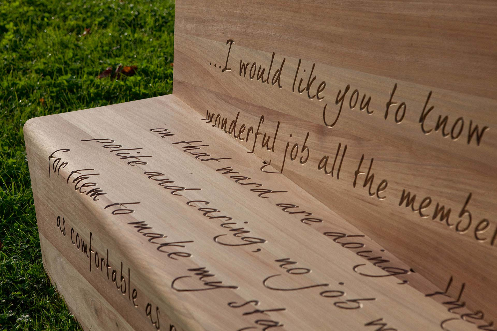 Positive and reassuring text engraved into oak bench