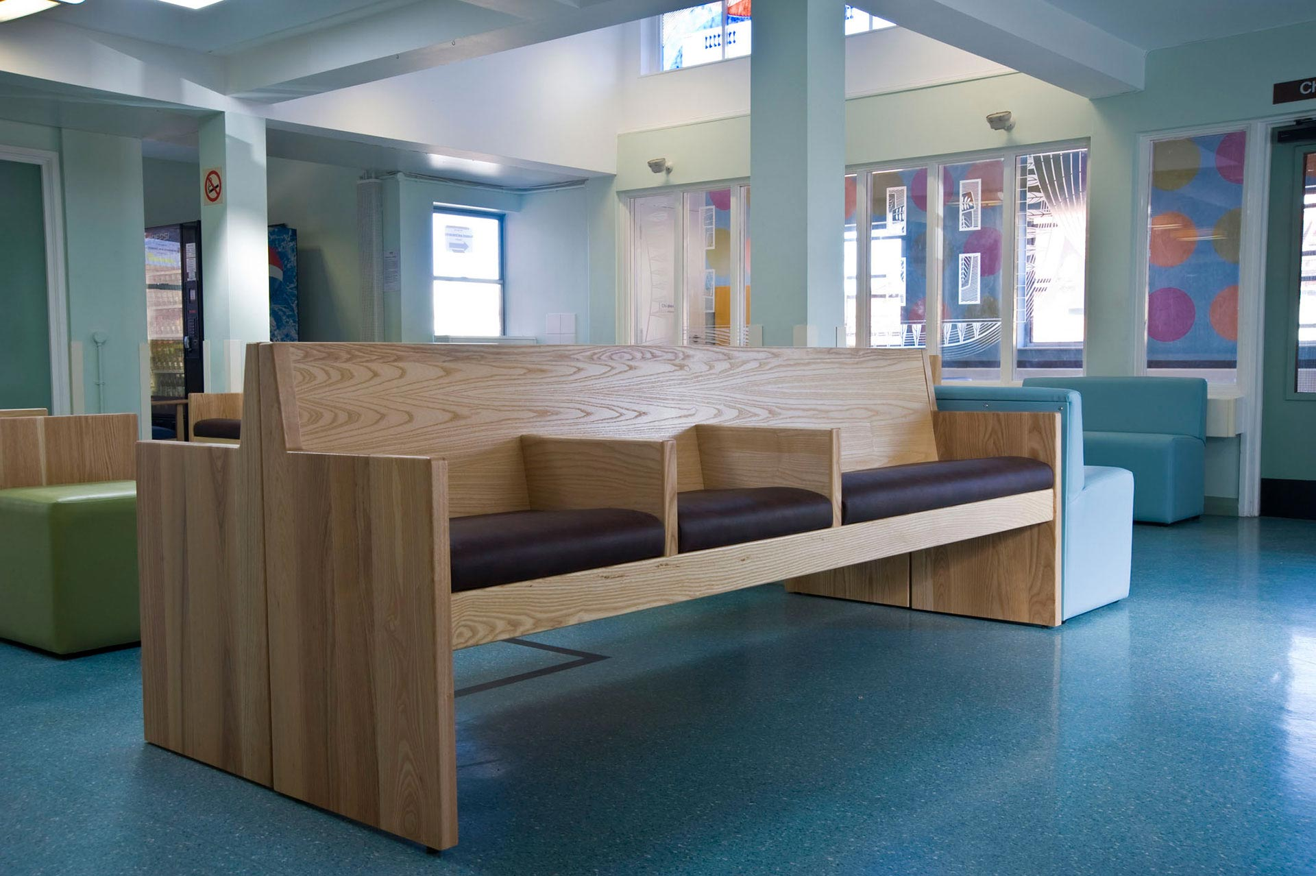 Informal groupings of pale ash timber seating in NHS waiting room