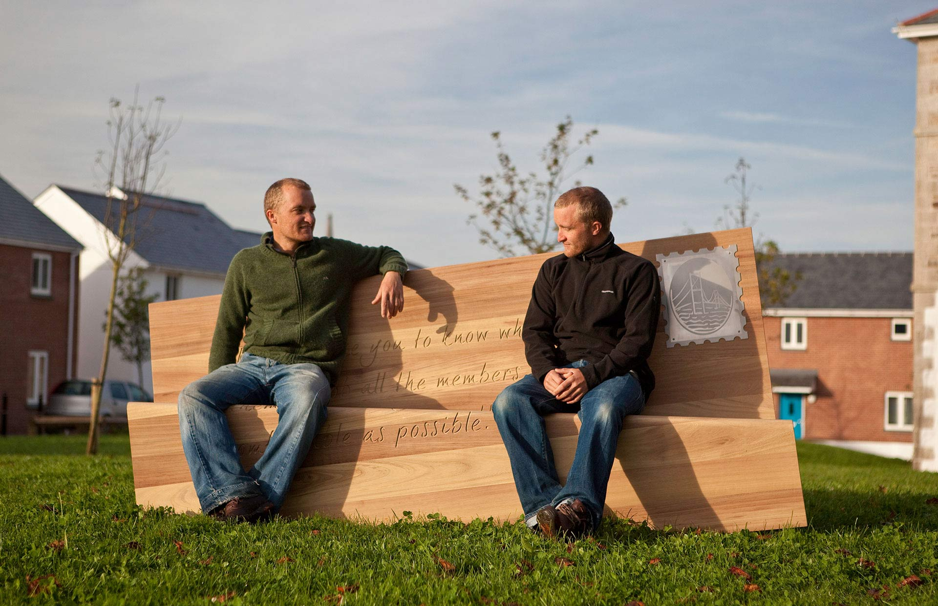 Sam and Will Boex sat on letter bench designed for Frenchay Hospital