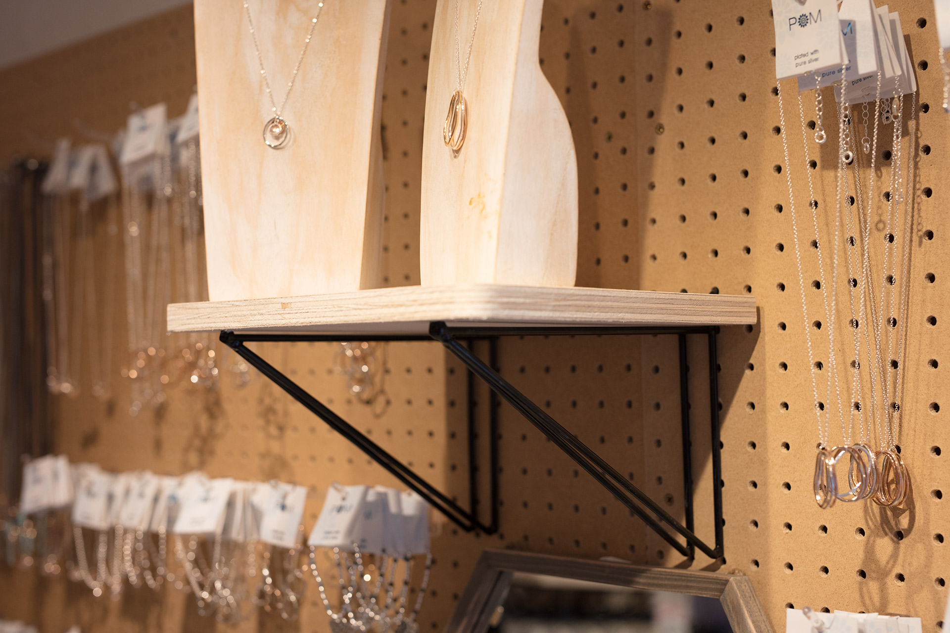 Bespoke wire brackets designed to fix to pegboard and support plywood display shelves