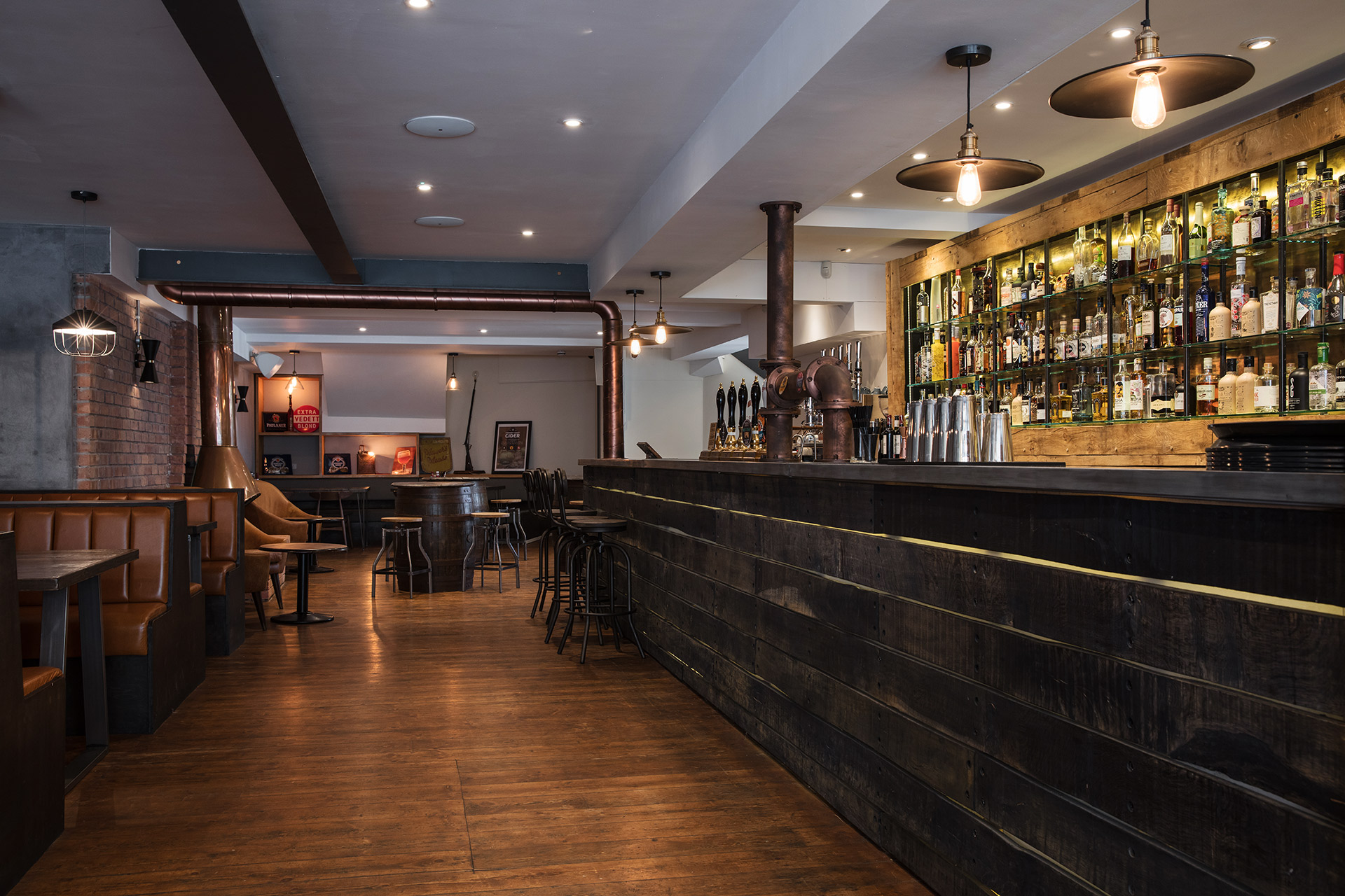 Banquette leather seating with blacked stained bar front with Zink Bar Top and brass beer font