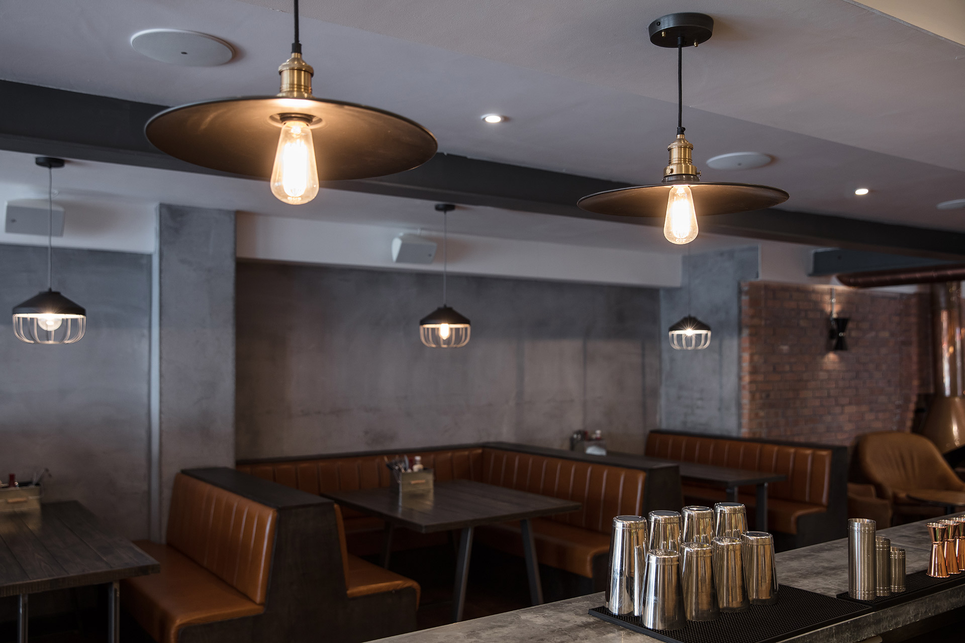 Leather banquet seating with concrete wall and exposed brick wall