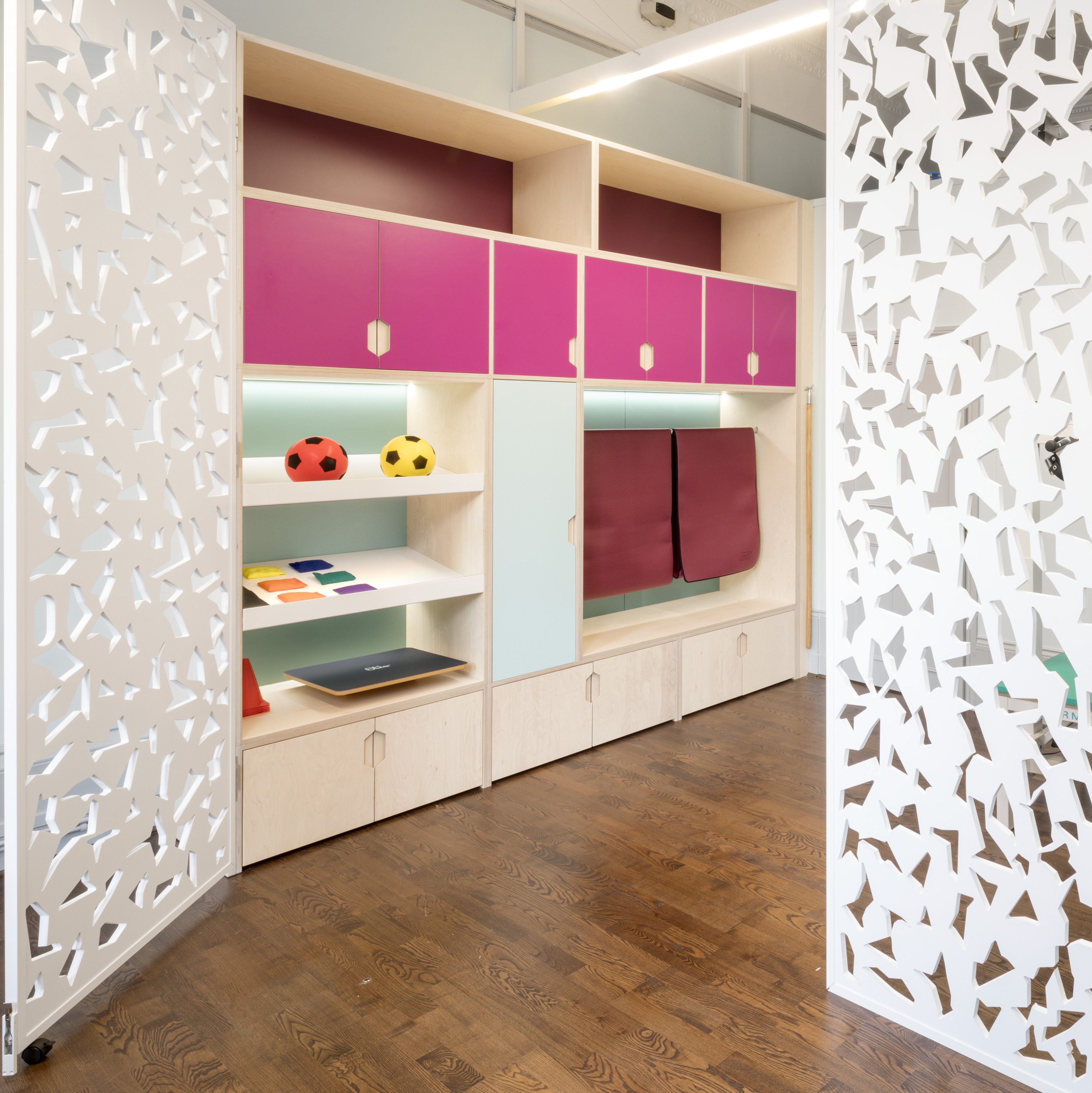 Custom storage units in pop colours and open shelving in healthcare clinic